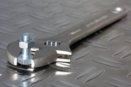 adjustable spanner, bolt and nut on diamond plate steel photo