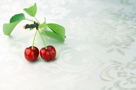 macro stusio shot of cherry fruit on white floral surface photo