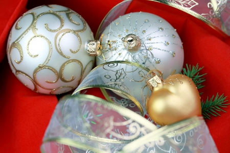 chrismas decorations  two silver baubles, golg heart and ribbon ot red velvet background