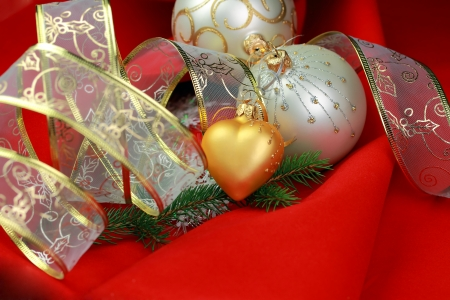 chrismas decorations  two silver baubles, golg heart and ribbon ot red velvet background photo