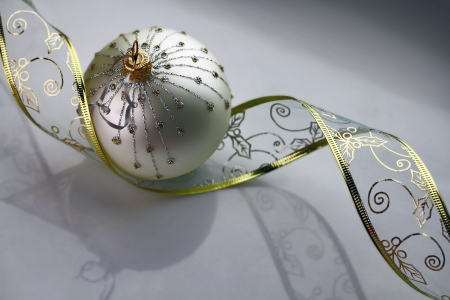 chrismas decorations  silver bauble and colden ribbon gray background