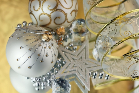 Two Christmas baubles, cristal sphere, star and ribbon on golden backgroud with reflections Standard-Bild