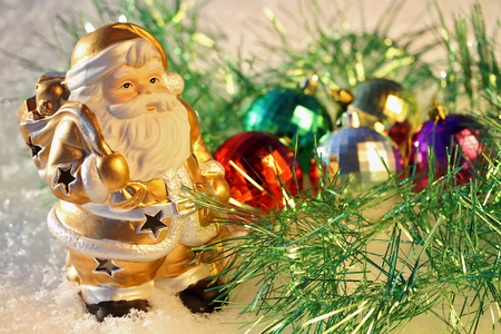 christmas ground: Gold Santa toy standing on snowy ground in front of Christmas Decoration