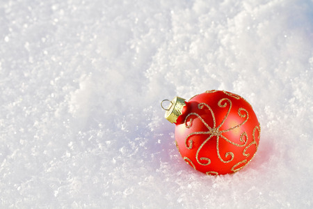 christmas ground: red Christmas Bauble on snowy ground