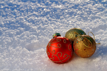red and golden Christmas Baubles on snowy ground