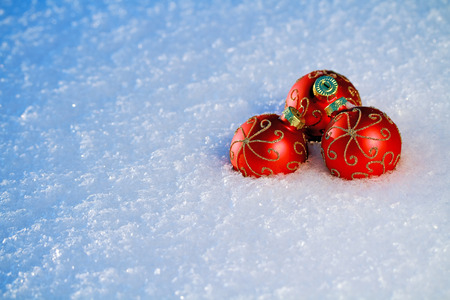 red Christmas Baubles on snowy ground