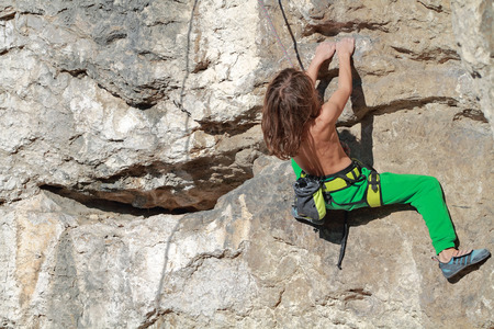 Young boy rock climber in search of for his next grip