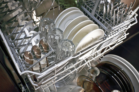 major household appliance: open dishwasher with clean plates in it