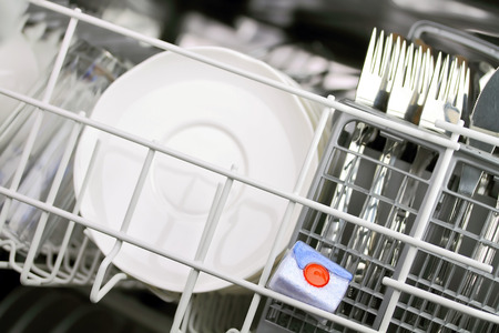 major household appliance: open dishwasher with clean plates in it, focus on dishwasher tabs