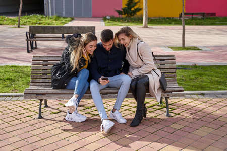 Three young friends sitting outdoors and looking at their cell phones. A group of people sitting on a park bench outdoors and watching a video on their smartphone. Concept of friendship and technology