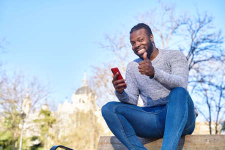 Smiling black man sitting on bench at park and using his smartphone, copy space