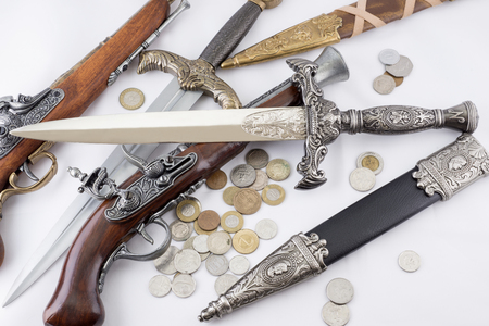 daggers: Old military daggers, guns and coins on white background