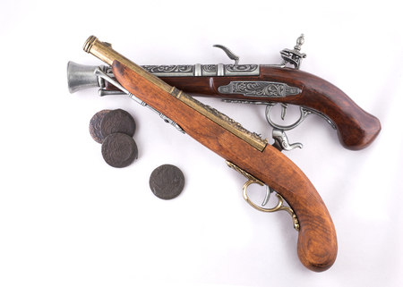 Old wooden guns and coins on white background