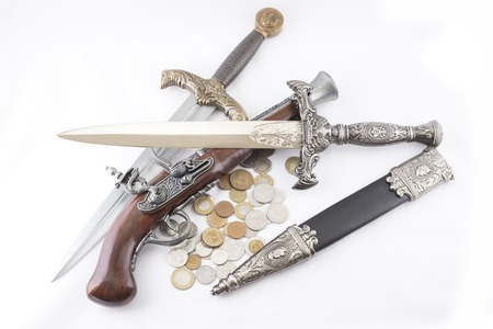 daggers: Old military daggers, gun and coins on white background