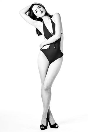 B&W of beautiful young brunette woman in swimsuit and black heels, on white background photo