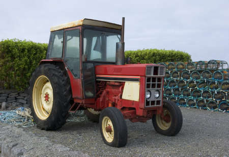 Vintage red tractor in front of a pile of lobster pots, photographed in Connemara, County Galway, Ireland photo