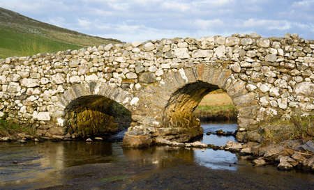 double reed: Evening light on an old crooked bridge over a trout stream in Connemara, County Galway, Ireland