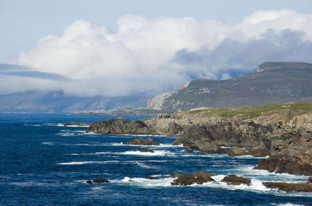 achill: Atlantic waves break on the rocky coast of Achill Island in the west of Ireland, sheep graze on the cliff top and a heather covered mountain in the distance catches the sunlight.