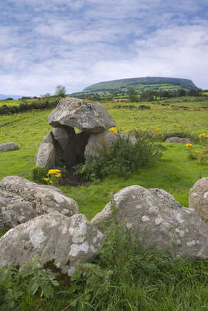 sligo: Ancient megalithic tomb at Carrowmore, County Sligo, Ireland.  A cairn on Knocknaree hill in the background marks the legendary grave of Queen Maeve of Connaught. Stock Photo