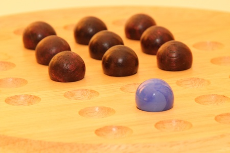 A blue marble stands out from some brown wooden marbles