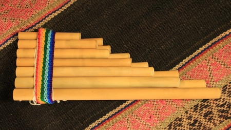 An Andean pan flute (known as a zampoña) on a traditional Andean textile. Stock Photo