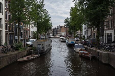 Canal in Amsterdam with the building known as Swaying Sisters in the background, Netherlands Stock fotó