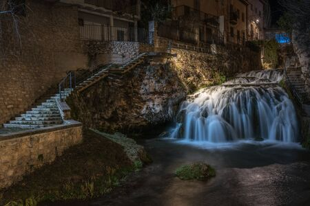 Trillo nightscape with a waterfall and the river crossing the center of the village, Guadalajara, Spain.