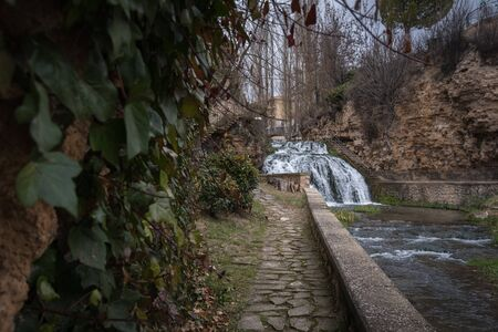 A waterfall of the Cifuentes river when it passes through the village center of Trillo, Guadalajara, Spain.