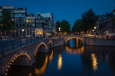 Scenic canals with illuminated bridges run throughout the city at night, Ámsterdam, Netherlands