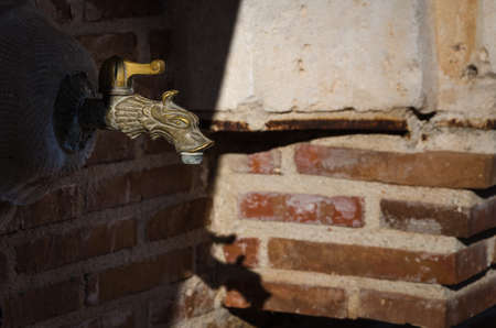A water tap and its shadow on a bricks wall