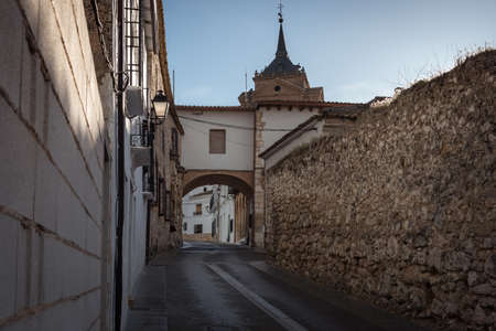 Uclés Old Town streets with a porch and the church dome in the background, Cuenca, Spain