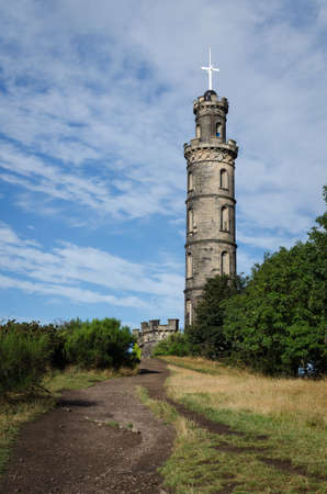 Nelson Monument on Calton Hill on a day with clouds and blue sky, Edinburgh, Scotland