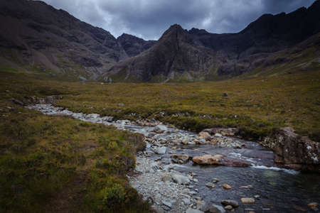 River in the Fairy Pools on the Isle of Skye under a stormy sky, Scotland, United Kingdom