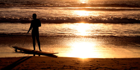 serine: Surfer with surf board on the ocean beach at sunset Stock Photo