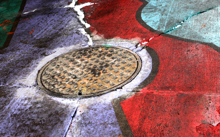 d       cor: Urban Art Manhole Cover Painted Rainbow Stock Photo