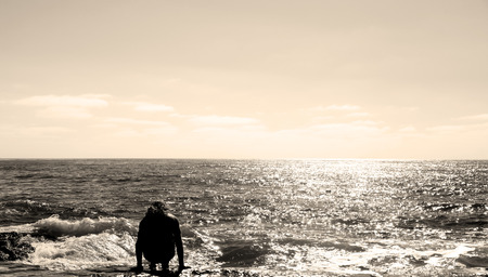 serine: Man sitting at the ocean beach