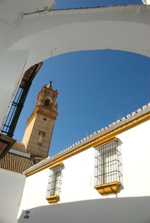 This tower belongs to Saint Philip church. It is seen through an arch in a typical street of Carmona (Seville) Stock Photo