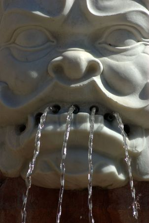 monster face: A monster face in a public fountain in SEville Stock Photo