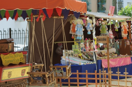 carmona: Carmona (Sevilla), Spain, 9th June 2013: Street Photography. Medieval Market. Vintage roundabaout and booths