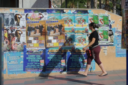 pgotography: Almu�ecar  Granada  Spain  18th July 2013 - Street pgotography - Lady walking in front of some posters