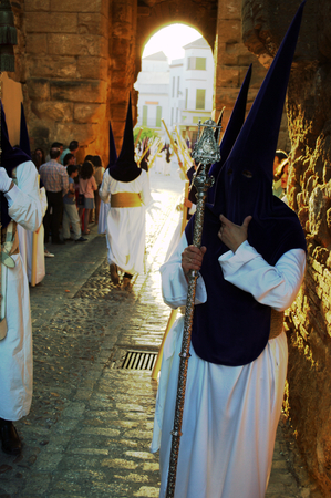 carmona: Carmona  Seville  Spain, 16th April 2014  Holy Week celebbrations  Penitents through an old arch 8