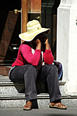 threshold: Sevilla - Spain - 19 July 2015 Urban life - Lady sitting on a house threshold