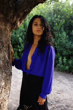 81: By a tree trunk in a blue blouse 81