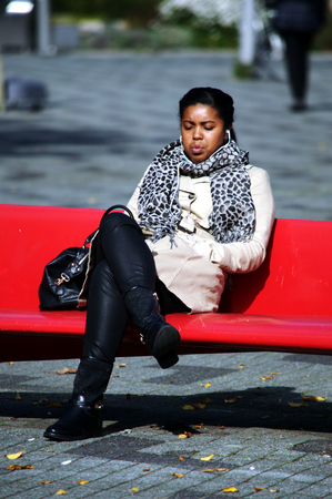 rotterdam: Netherlands, Rotterdam, 11th October 2015 - Young black lady sitting in the street