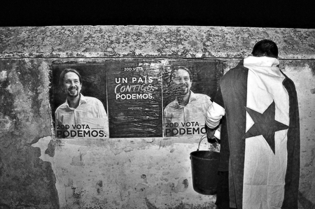 election night: Carmona, Sevilla, Spain, 4th December 2015 - PODEMOS militants hanging posters for the electoral campaign