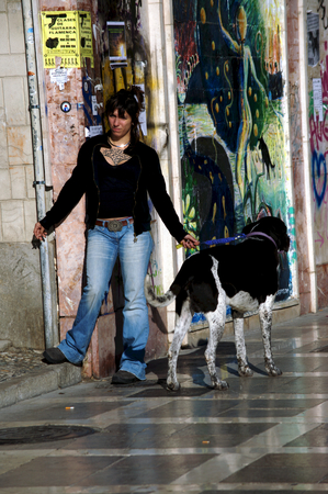 painted dog: Granada - Spain 26th December 2011 - Urban life - Young lady with dogs by graffitis