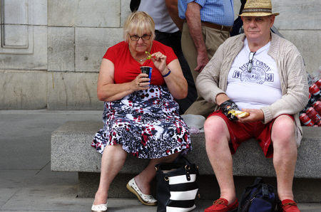 Seville, Spain, 14th September 2016 - Couple of fat senios sitting in the street Editorial
