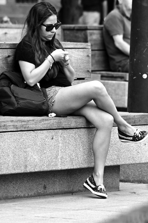 Seville, Spain, 14th September 2016 - Young lady sitting in the street Editorial