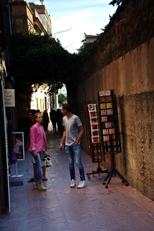 Seville, Spain, 14th September 2016 - People in a narrow street in the old area of the city