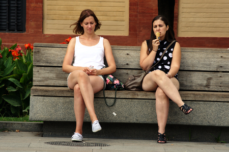 Seville, Spain, 14th September 2016, Young ladies sitting in the sun and eating an icecream